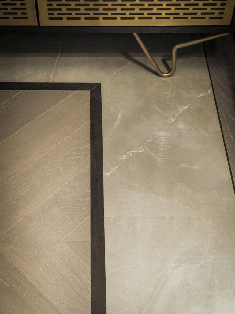 timber flooring in an interesting pattern with marble inlays or borders and brass trims