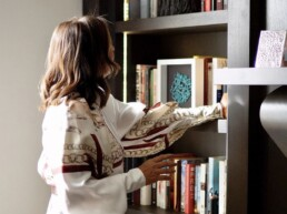 shalini misra next to bookcase