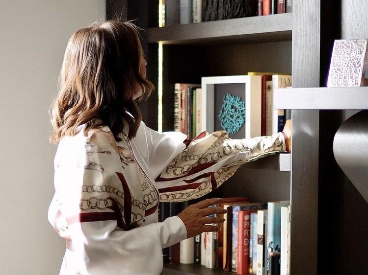 shalini misra next to bookcase